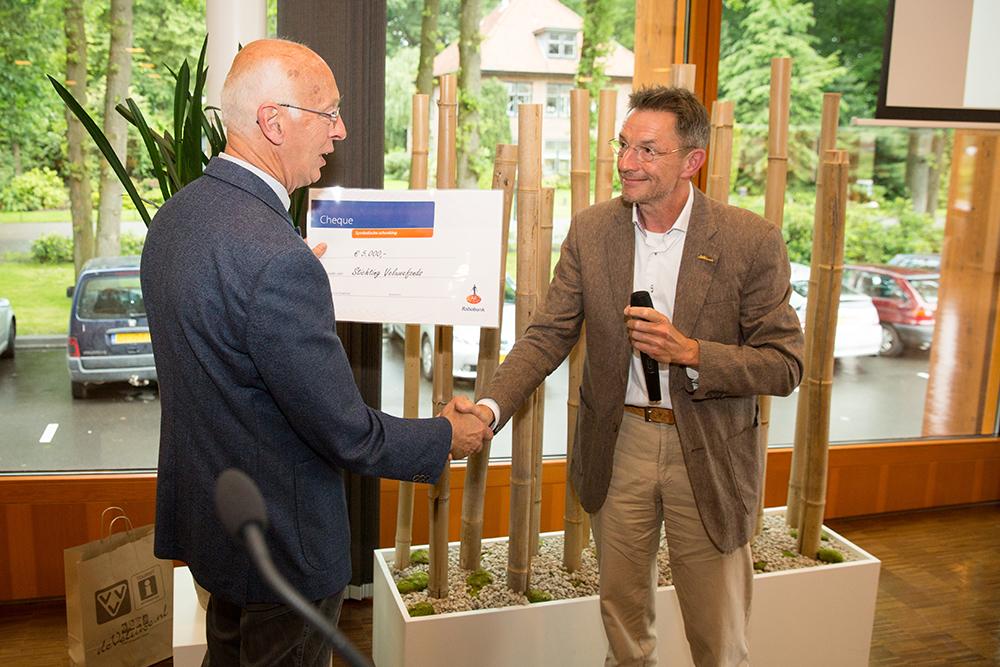 Jan van Muyden van het Veluwefonds ontvangt de cheque van Jac Meter van het Nationaal Groenfonds
